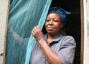 A woman putting up a mosquito bednet, United Republic of Tanzania.